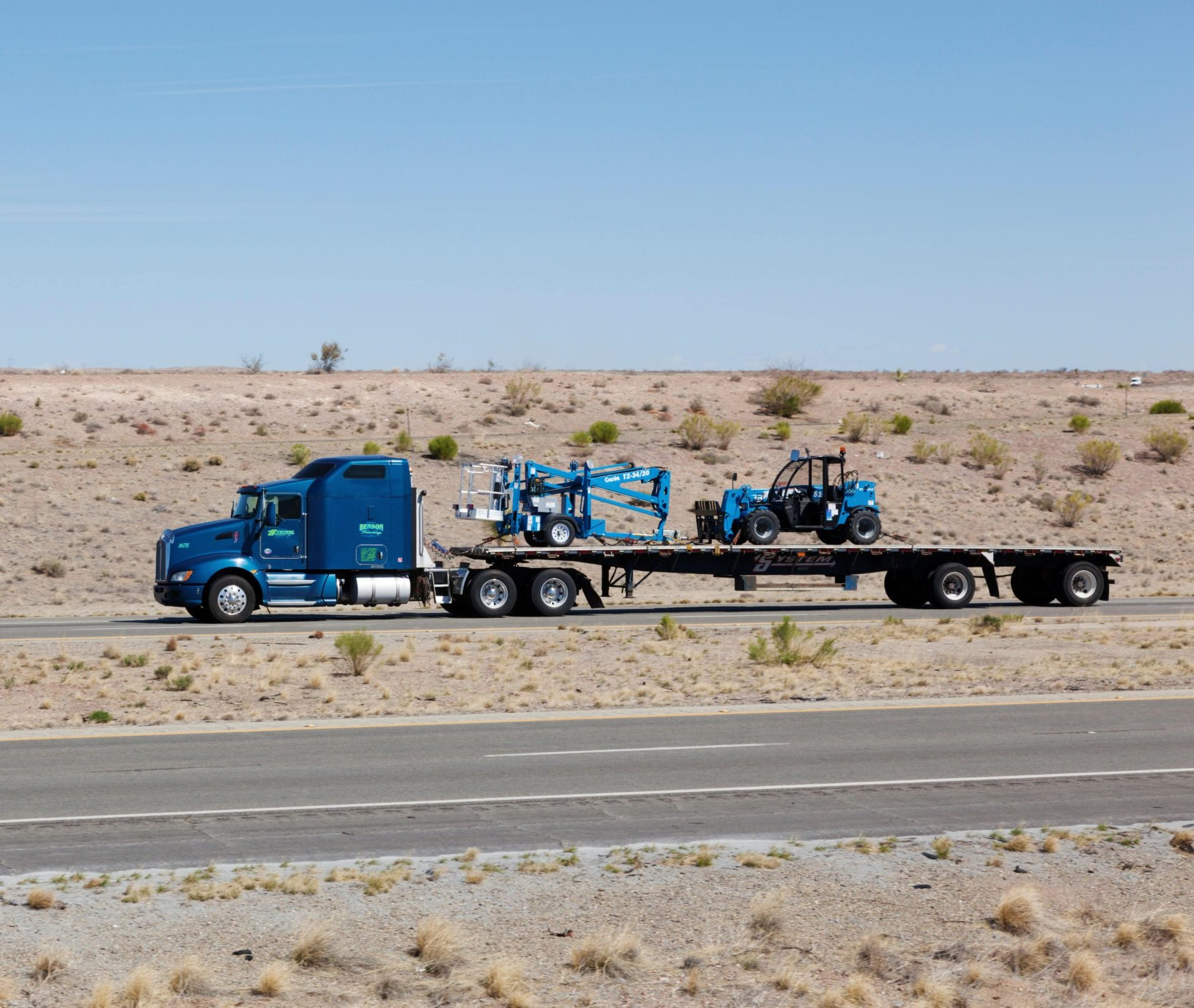 Truck hauling forklifts in transport