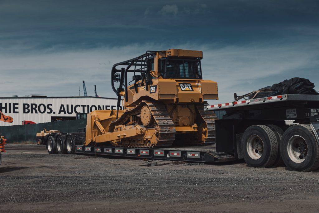 Open deck trailer transporting a bulldozer