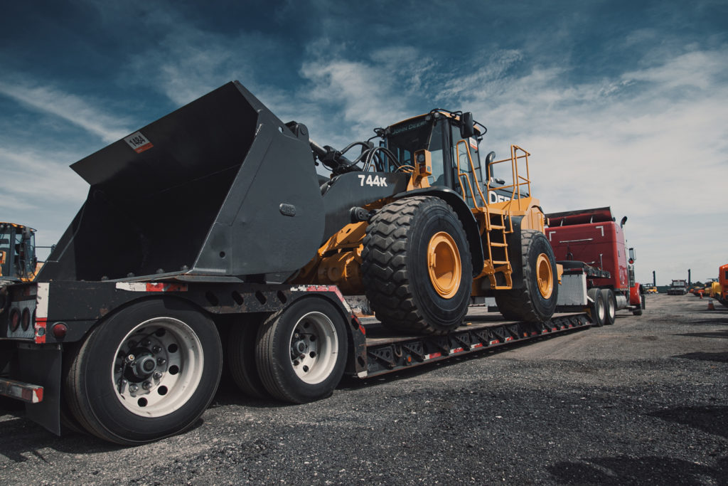 A lowboy trailer hauling a wheel loader.